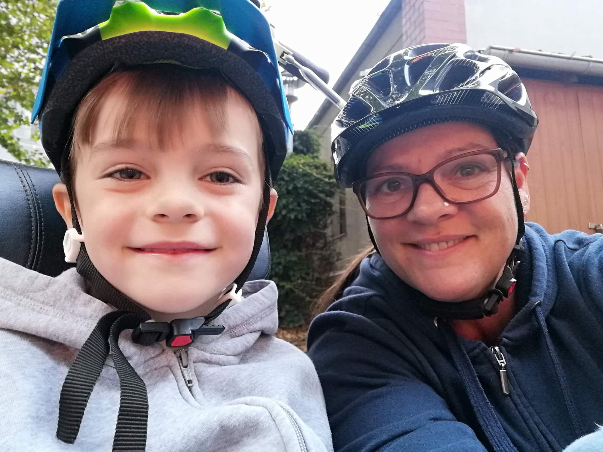 Selfie von Mutter und Sohn, die fröhlich lachen und beide einen Fahrradhelm tragen