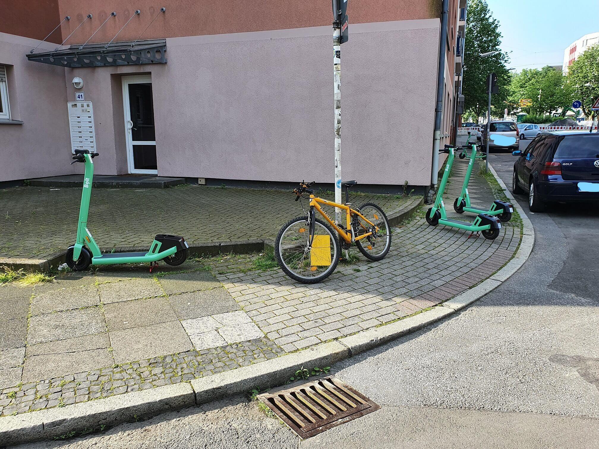 Drei gelbe E-Scooter und ein grünes Fahrrad, welche auf dem Gehweg abgestellt wurden.