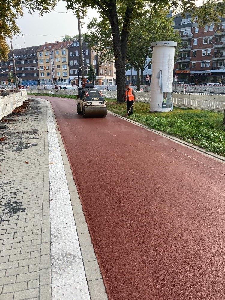 Eine Walze fährt über den frisch asphaltierten Radweg am Wall in Dortmund.