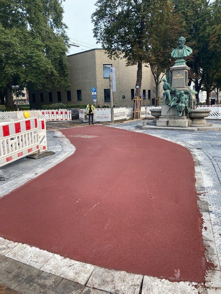 Ein auffällig rot asphaltierter und breiter Fahrradweg der eine leichte Linkskurve macht mit Bäumen am Wall in Dortmund