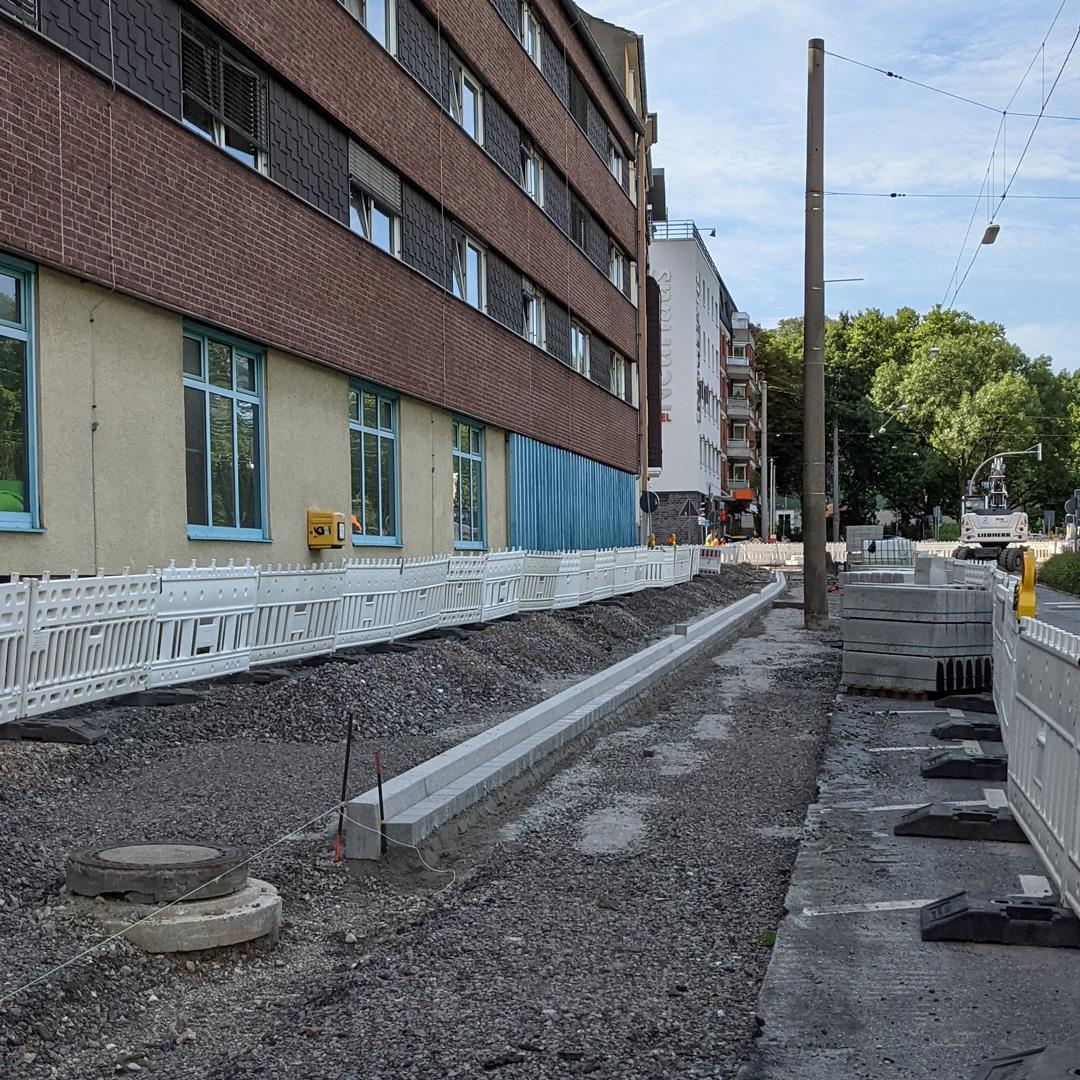 Baustelle entlang einer Häuserfront am Wallring Dortmund mit noch offenem Kiesuntergrund und verlegten Steinen für den Bordstein