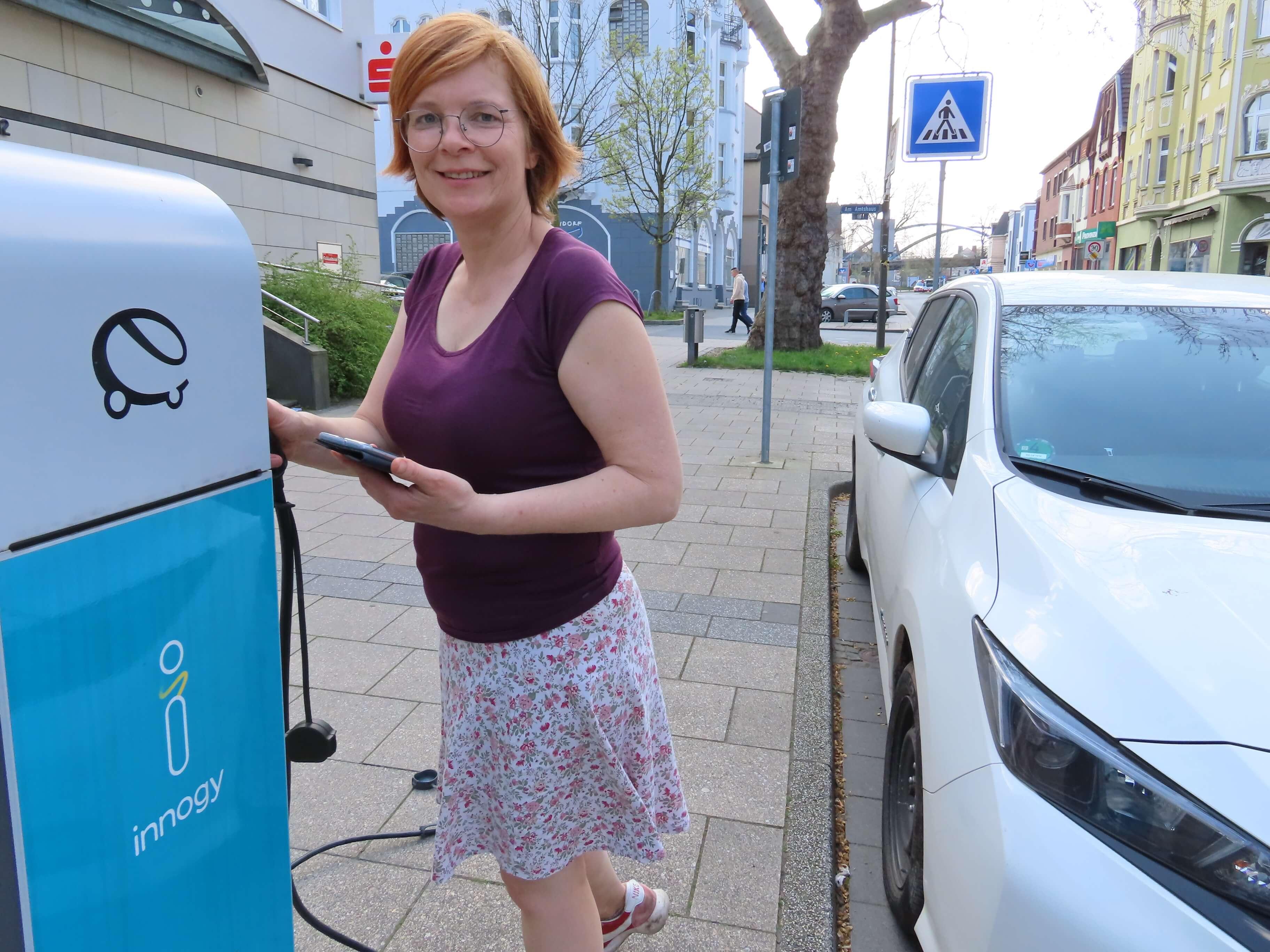 UmsteiGERN-Botschafterin Christine lädt ihr E-Auto an einer Ladesäule in Dortmund