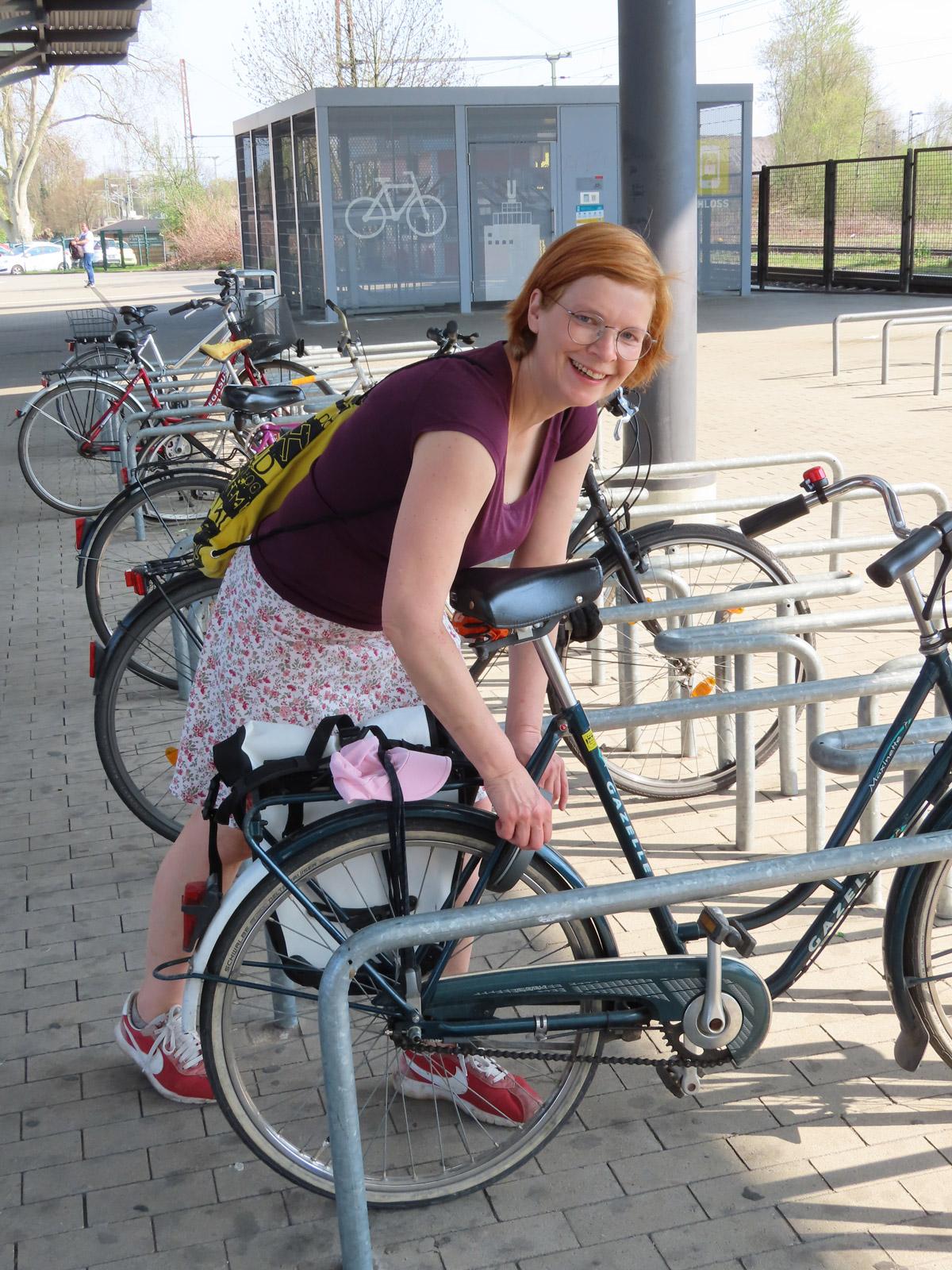 UmsteiGERN-Botschafterin Christine schließt ihr Rad an der Bike-and-Ride-Station ab