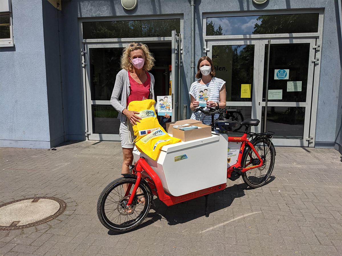 Zwei Frauen stehen hinter einem roten Lastenfahrrad mit Umsteigern-Logo auf dem Laderaum mit Umsteigern-Jutebeuteln und Mobilitätsfibeln in der Hand