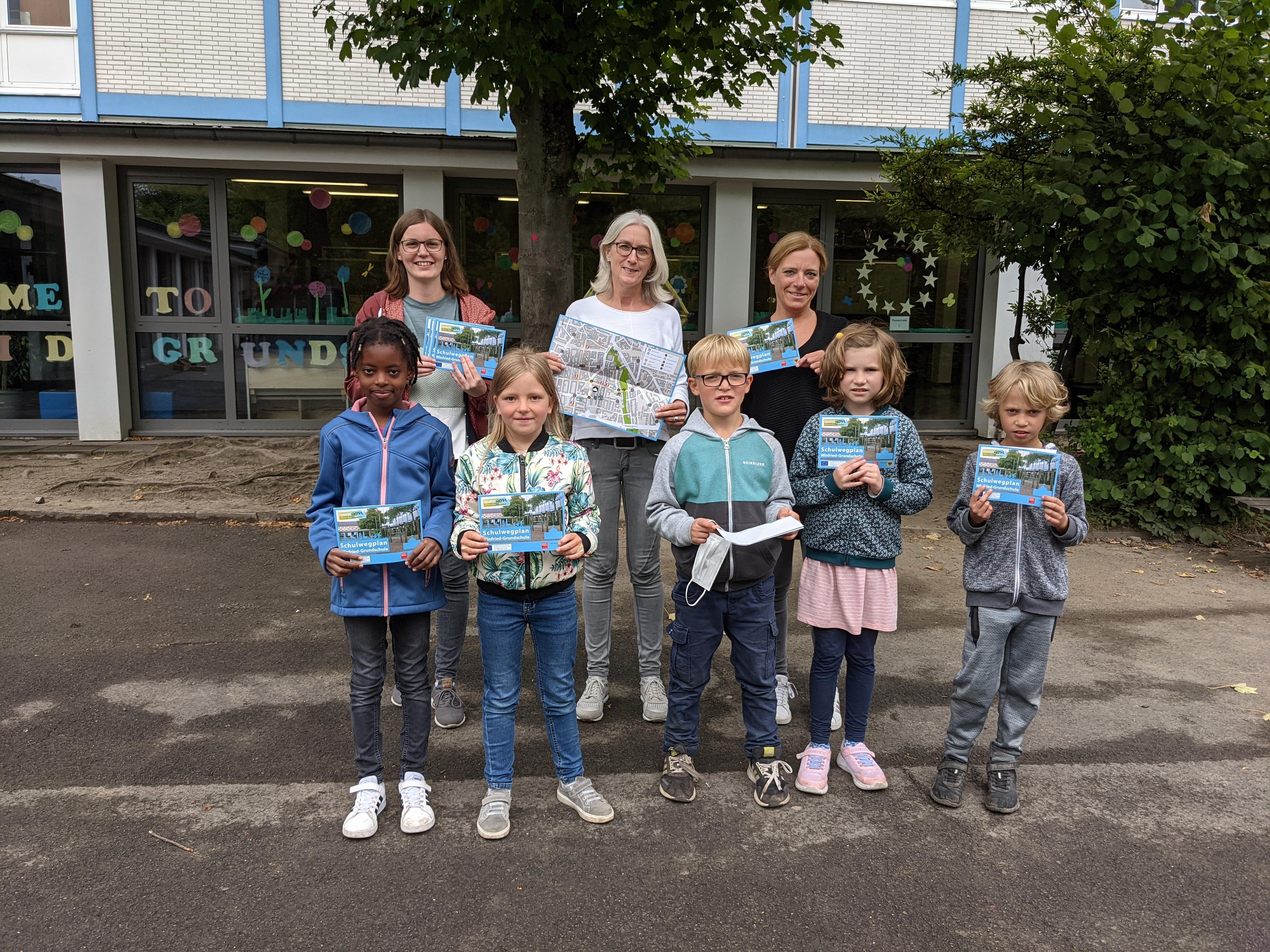 Fünf Grundschüler und Grundschülerinnen sowie drei Lehrerinnen halten Schulwegplan für ihre Grundschule in Dortmund in der Hand
