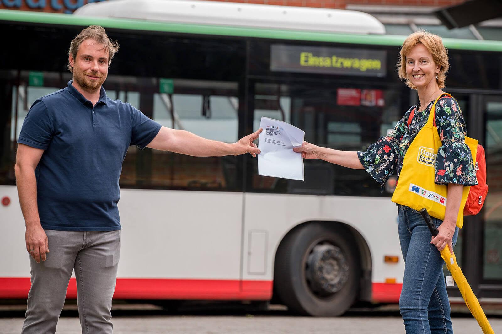 Zwei Personen stehen vor einem Bus und halten zwischen sich gemeinsam einen Ticket, in Form eines DIN A4 Zettels, für den ÖPNV hoch.