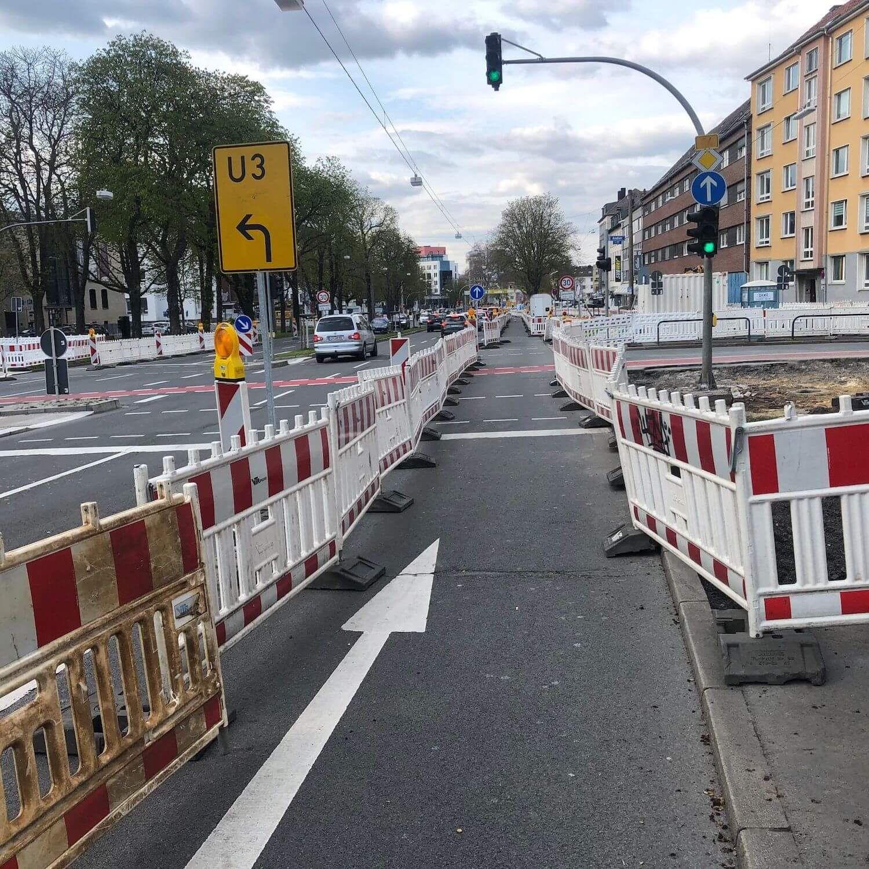 Ein Baustellenweg für Fußgänger an einer großen Kreuzung mit Ampeln und Schildern.