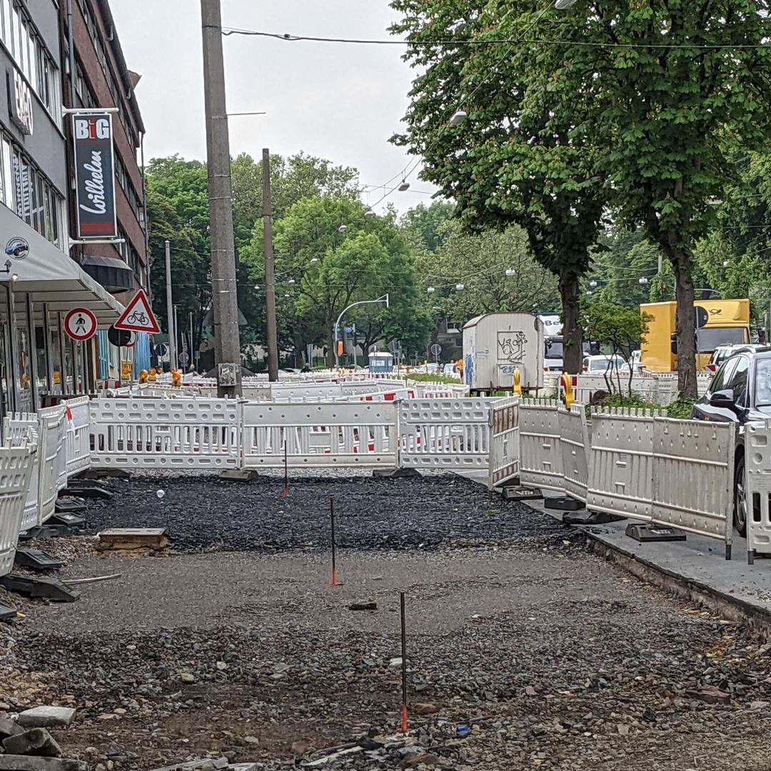Baustelle am Radwall umzäunt von Bauzaun mit erkennbaren Schichten aus verschiedenen Baumaterialen für den Straßenbelag