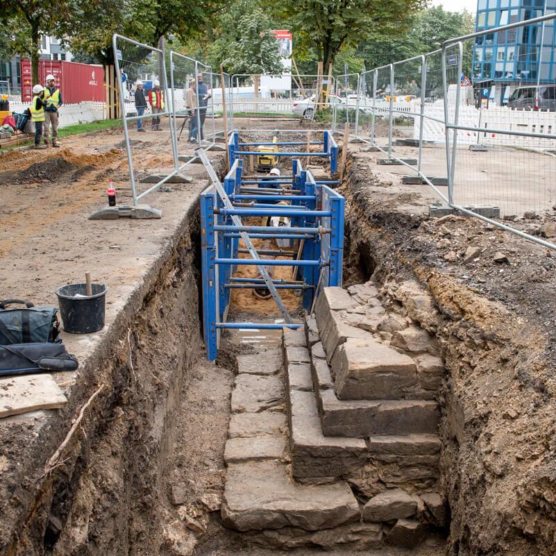 In einem Baugraben am Wallring ist eine alte Treppe aus groben Steinen zu sehen, die ordentlich ausgegraben wurden