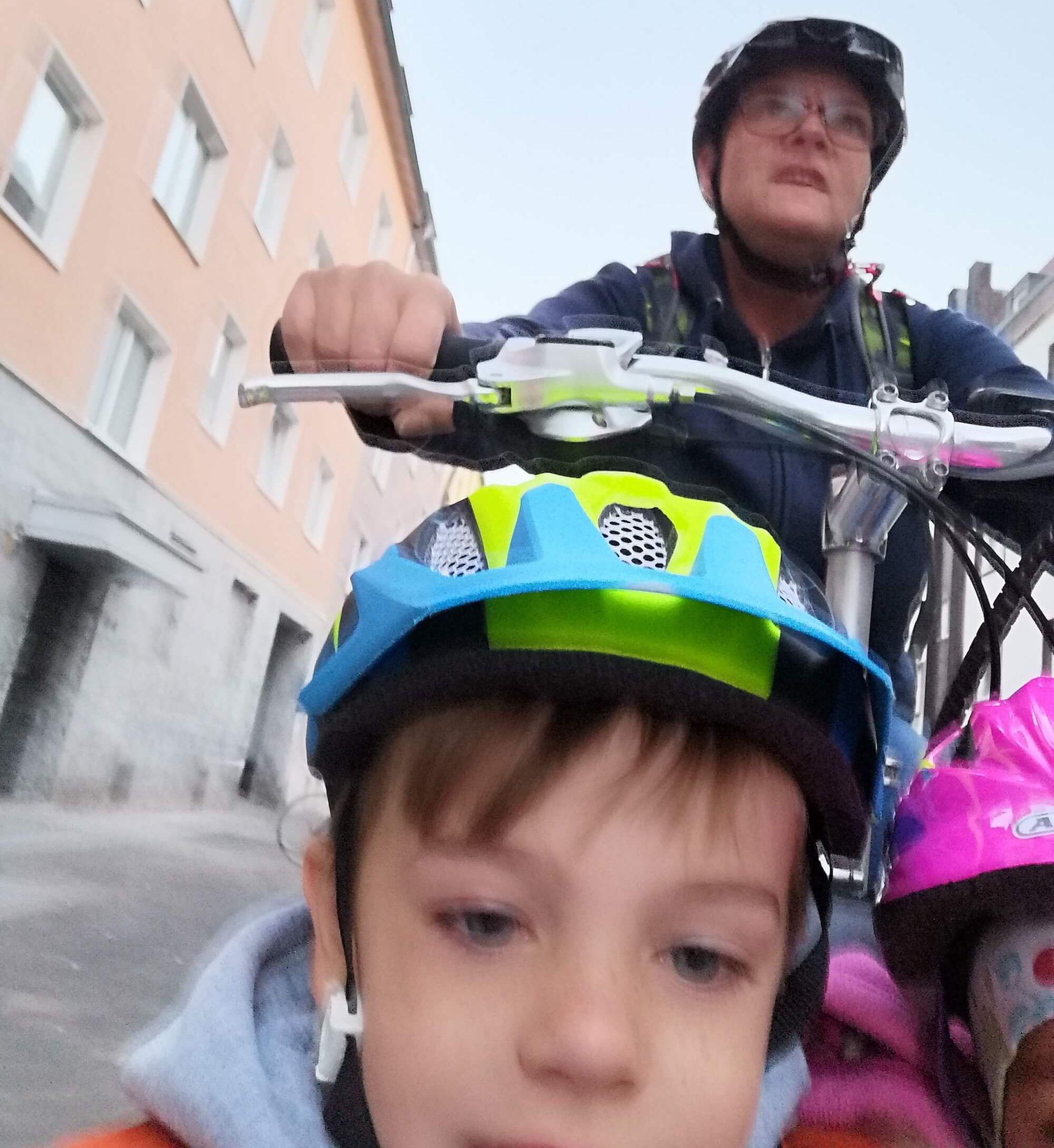 Selfie aus der Sicht eines Jungen, der im Kindersitz eines Lastenrads sitzt, auf dem Sattel sieht man im Hintergrund seine Mutter