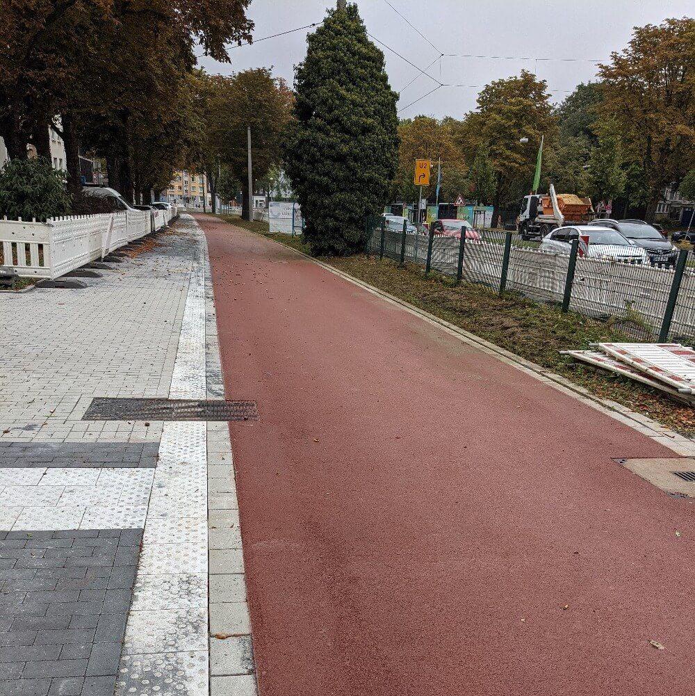 Frisch asphaltierter roter Radweg mit neuem Bürgersteig und Bodenleitsystem im Wall in Dortmund im Rahmen des Projekts UmsteiGERN