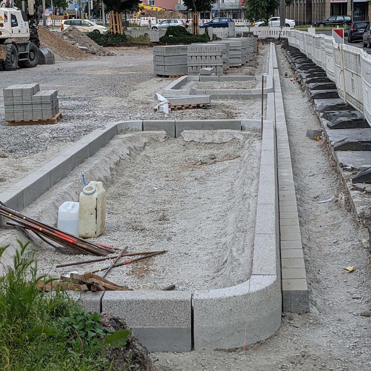 Baustelle des Radwegs am Wallring mit Blick auf das Mikrodepot in Dortmund mit verlegten Pflastersteinen als Begrenzung am Rand und Schotter in der Wegmitte