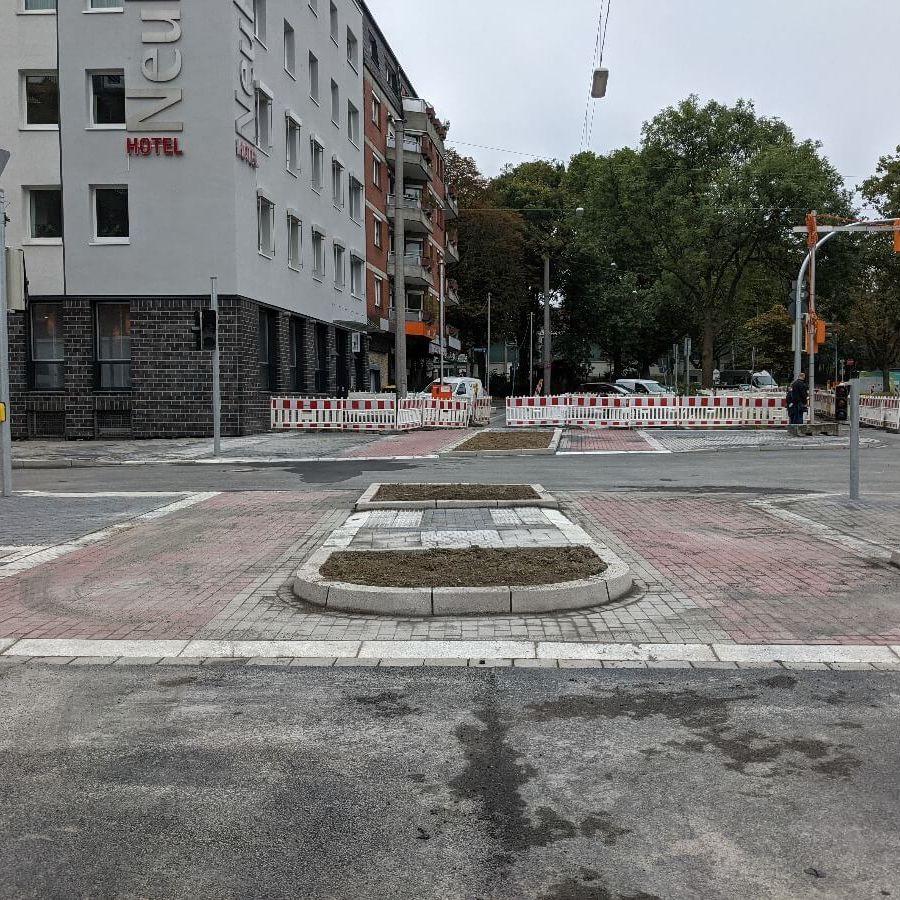 Frisch gepflasterte Straßenkreuzung mit breiten Radwegen und Radampeln am Ostwall in Dortmund