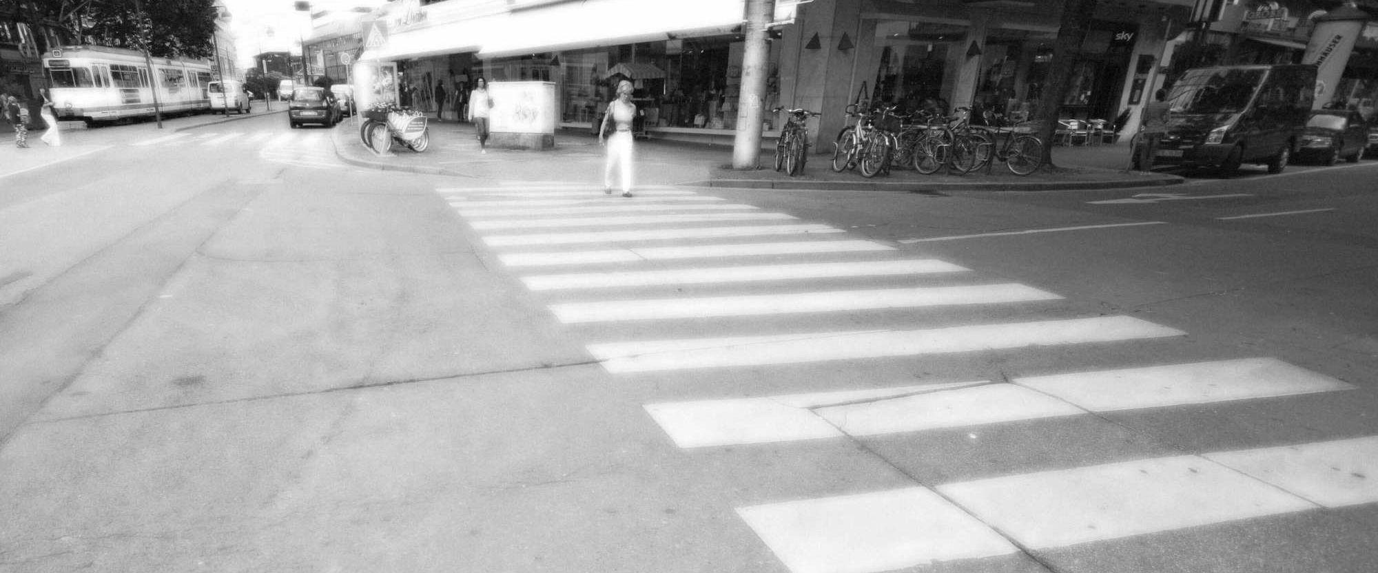 Eine verschwommen dargestellte Frau geht über einen Zebrastreifen.