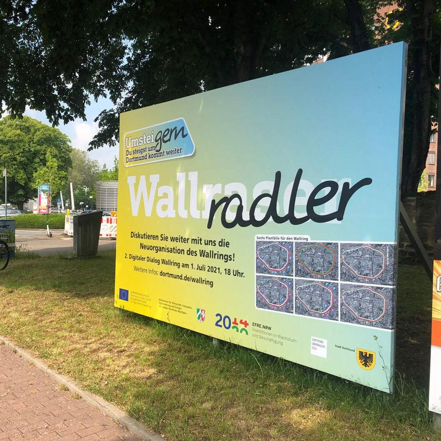 Foto eines UmsteiGERN-Plakats zur Dialogveranstaltung zum Wallring vor grünen Bäumen am Wallring in Dortmund
