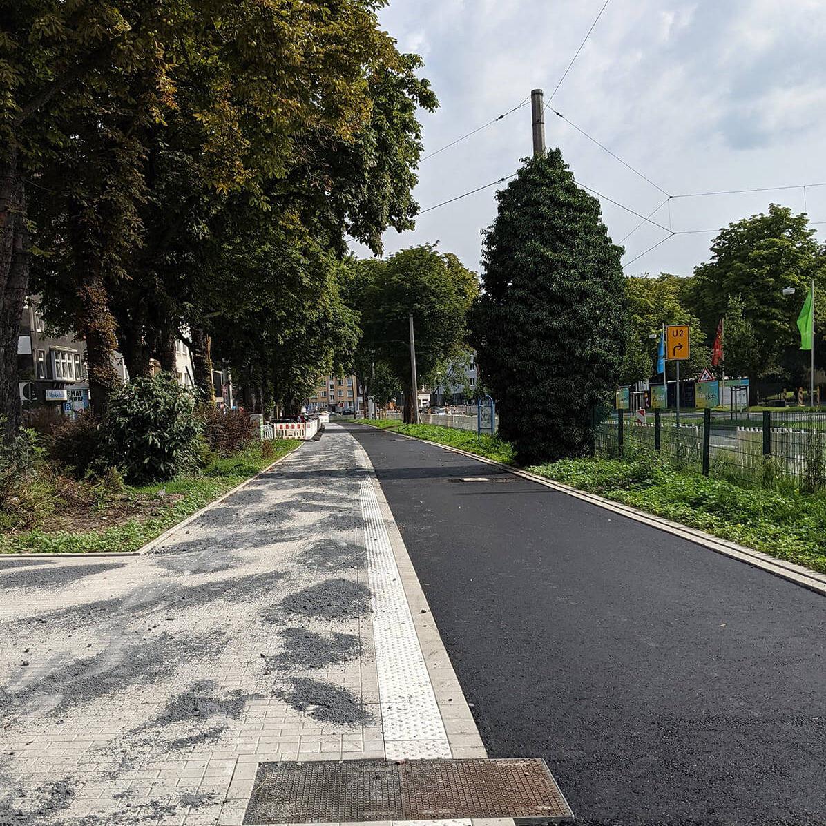 Frisch asphaltierter Radweg und gepflasterter Gehweg in Dortmund für den Radwall umgeben von grünen Bäumen