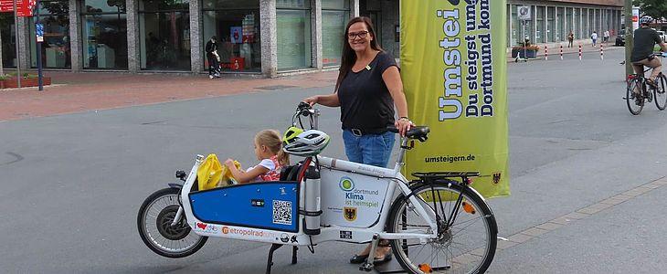 Frau steht lächelnd hinter Lastenrad, in dessen Kindersitz ihre Tochter sitzt