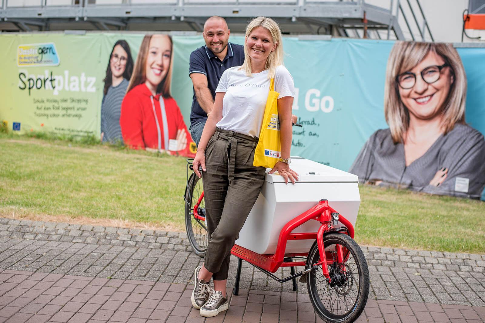 Eine junge Frau lehnt sich entspannt und lächelnd auf die Transportbox des roten UmsteiGERN-Lastenrads währen ein junger Mann auf dessen Sattel sitzt. Im Hintergrund sieht man Werbeplakate von UmsteiGERN.