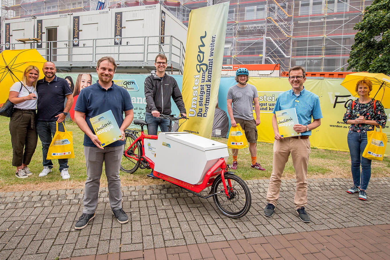 """Sechs Personen stehen mit ca. 1,5 m Abstand zu einander vor Werbebannern von """"UmsteiGERN"""". Sie präsentieren das UmsteiGERN-Lastenrad, die """"Umdenkmappe"""" und UmsteiGERN-Schirme für die Aktion Lappenlos"""