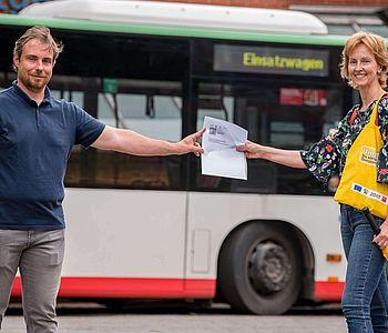 Eine Frau, welche einem Mann, ein Ticket anreicht. Im Hintergrund ist ein Linienbus abgebildet.
