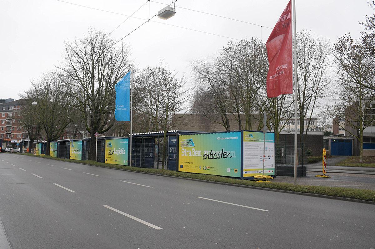 Mehrere Schiffscontainer mit Umsteigern-Farben und Logo stehen auf Parkplatz am Wallring als Mikrodepot