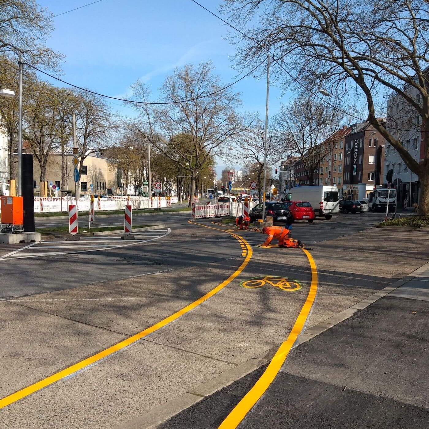 Ein Baustellenarbeiter trägt die Radstreifen Markierung am Ostwall auf die Straße auf.