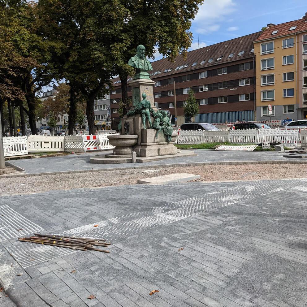 Frisch gepflasterter Gehweg rund um das Schüchtermann Denkmal in Dortmund bei sonnigem Wetter